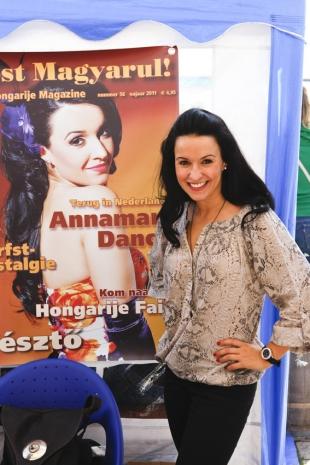 Annamari Dancs poseert in de stand van Most Magyarul! Hongarije Magazine vóór de poster van de cover met haar portret van Most Magyarul! nummer 56.